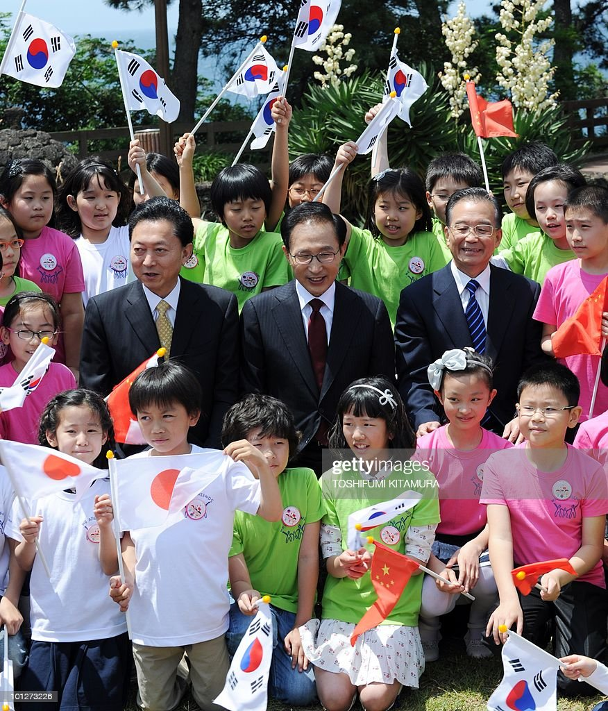 South Korean President Lee Myung-Bak (C), Japanese Prime Minister Yukio Hatoyama (L) and Chinese Premier Wen Jiabao (R) and children with the three nations' flags pose for photos during a time capsule laying ceremony in Seogwipo on May 30, 2010, the second-day of trilateral summit meetings. Hatoyama and Wen were in South Korea to a attend the trilateral summit to discuss the sinking of the South Korean warship, Cheonan, which claimed 46 lives and is blamed on North Korea. Wen said May 30 there is an 'urgent' need to avoid clashes and ease tensions following the sinking.