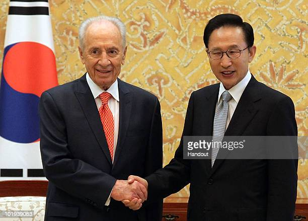 South Korean President Lee MyungBak shakes hands with Israeli President Shimon Peres during their meeting at the presidential blue house on June 10...