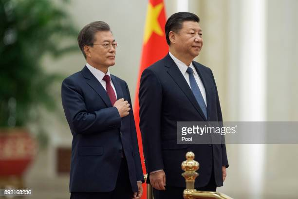 South Korean President Moon JaeIn and Chinese President Xi Jinping listen to the South Korean anthem during a welcome ceremony at the Great Hall of...