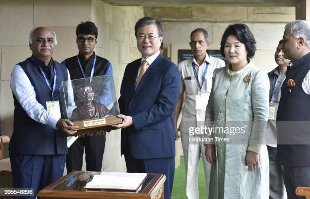 South Korean President Moon Jaein and his wife Kim Jungsook receive a bust of Mahtma Gandhi after paying homage at Rajghat on July 10 2018 in New...