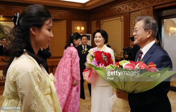 South Korean President Moon Jae-in and his wife Kim Jung-sook receive flowers as they arrive at Baekhwawon State Guesthouse where Moon will stay...