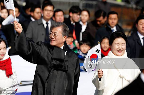 South Korean President Moon Jae-In and his wife Kim Jung-Sook wave the national flag during a march to commemorate the 99th Independence Movement Day...