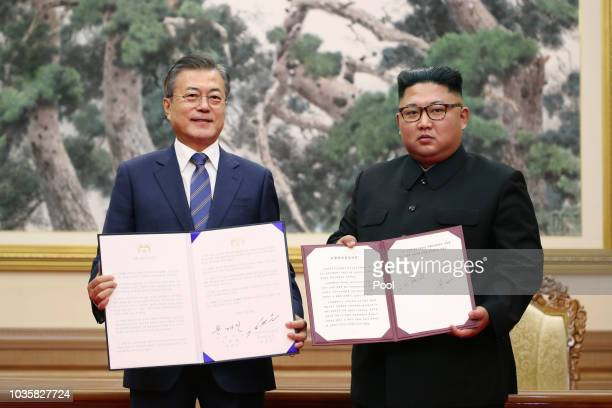 South Korean President Moon Jaein and North Korean leader Kim Jong Un pose for photographs during a signing ceremony at Paekhwawon State Guesthouse...