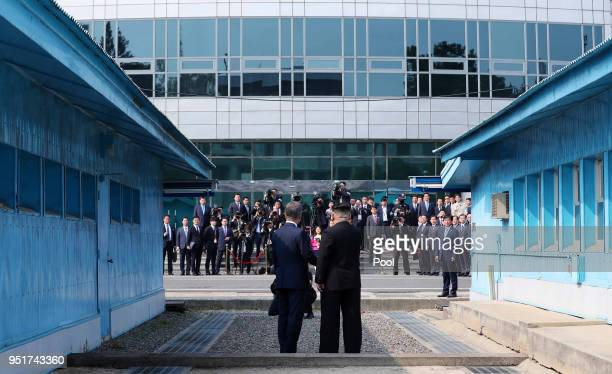 South Korean President Moon Jae-in and North Korean Leader Kim Jong Un shake hands upon meeting for the Inter-Korean Summit at the military...