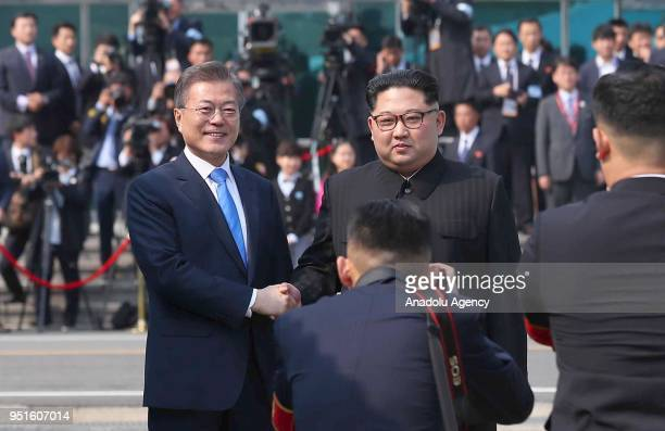 South Korean President Moon Jaein and North Korean leader Kim Jongun shake hands as they pose for a photo during a meeting at the southern side of...