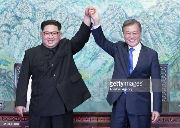 South Korean president Moon Jaein and North Korean leader Kim Jongun are raising hands after issuing a joint statement in the Peace House building at...