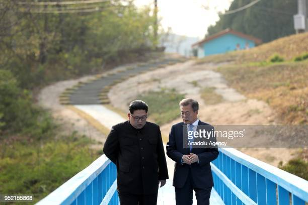 South Korean president Moon Jaein and North Korean leader Kim Jongun take a walk after planting a commemorative tree in the Peace House building at...