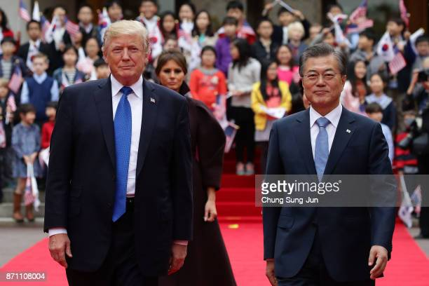 South Korean President Moon JaeIn and US President Donald Trump walk towards a guard of honour during a welcoming ceremony at the presidential Blue...