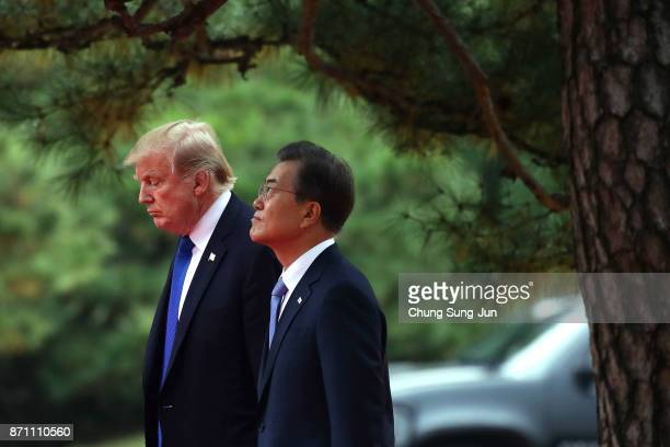 South Korean President Moon JaeIn and US President Donald Trump walk during a welcoming ceremony held at the presidential Blue House on November 7...