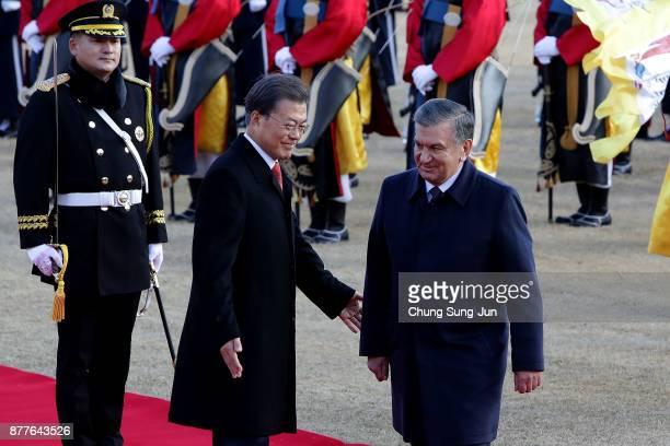 South Korean President Moon JaeIn and Uzbekistan President Shavkat Mirziyoyev walk towards a guard of honour during a welcoming ceremony at the...
