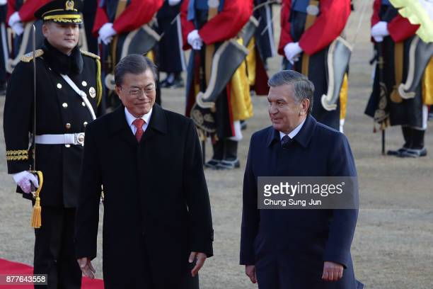 South Korean President Moon JaeIn and Uzbekistan President Shavkat Mirziyoyev walk towards a guard of honour during a welcoming ceremony at the...