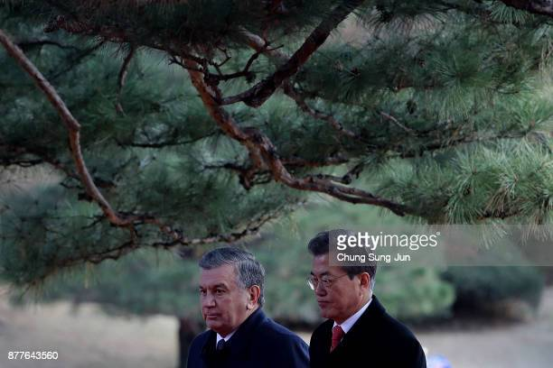 South Korean President Moon JaeIn and Uzbekistan President Shavkat Mirziyoyev walk during a welcoming ceremony at the presidential Blue House on...