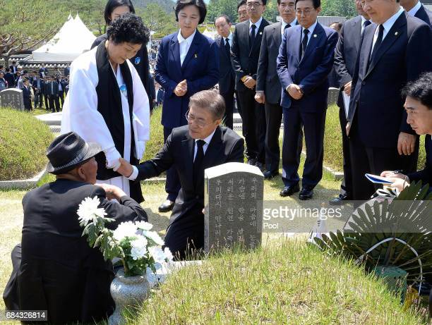 South Korean President Moon Jaein center consoles family members of the deceased in front of a grave marker during the 37th annual May 18 Democratic...