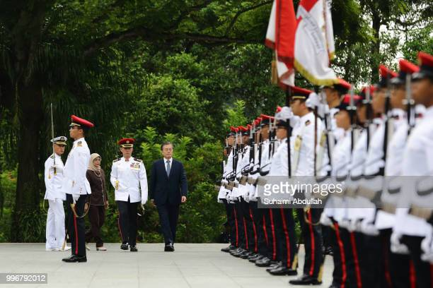 South Korean President Moon Jaein inspects the guard of honour accompanied by Singapore President Halimah Yacob during the welcome ceremony at the...