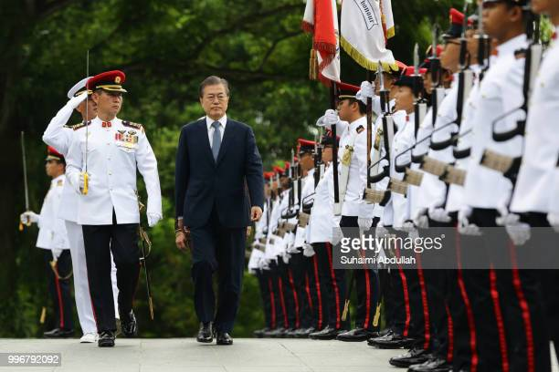 South Korean President, Moon Jae-in inspects the guard of honour, accompanied by Singapore President, Halimah Yacob during the welcome ceremony at...