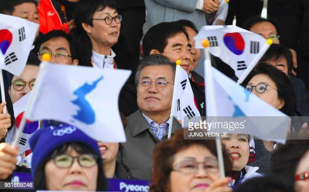 TOPSHOT South Korean President Moon Jaein is seen as spectators wave the national flag and 'unification flags' during the men's 11km sprint sitting...
