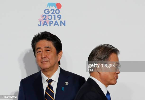 South Korean President Moon Jae-In is welcomed by Japanese Prime Minister Shinzo Abe before a family photo session at G20 summit on June 28, 2019 in...