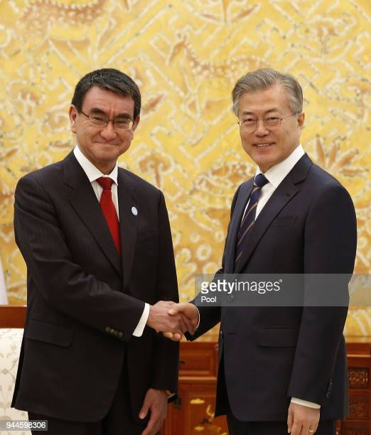 South Korean President Moon JaeIn shakes hands with Japanese Foreign Minister Taro Kono during their meeting at the presidential blue house on April...