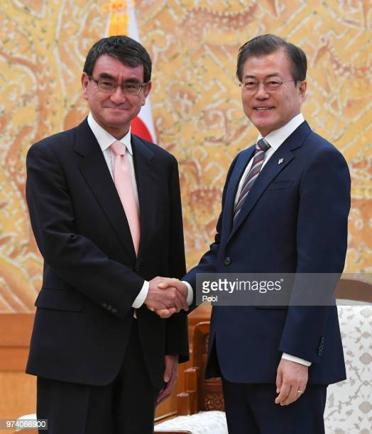 South Korean President Moon Jaein shakes hands with Japanese Foreign Minister Taro Kono during their meeting at presidential blue houes on June 14...