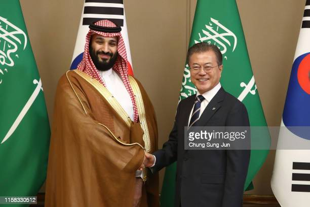 South Korean President Moon Jae-In shakes hands with Saudi Crown Prince Mohammed bin Salman during a meeting at the Presidential Blue House on June...