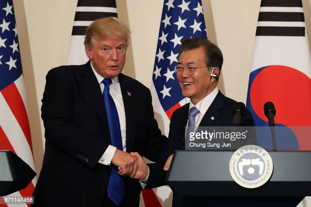 South Korean President Moon JaeIn shakes hands with US President Donald Trump during the joint press conference at the presidential Blue House on...
