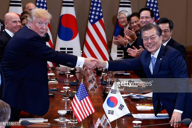 South Korean President Moon Jae-In shakes hands with U.S. President Donald Trump during their summit at the presidential Blue House on November 7,...