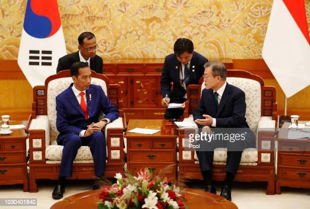 South Korean President Moon JaeIn talks with Indonesian President Joko Widodo before their meeting at the Presidential blue house on September 10...