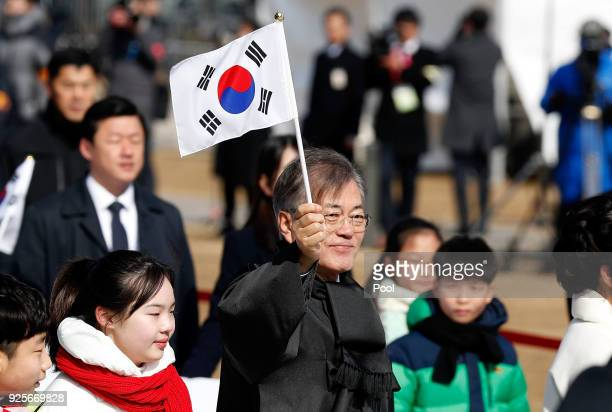 South Korean President Moon Jae-In waves the national flag during a march to commemorate the 99th Independence Movement Day ceremony at Seodaemun...