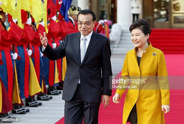 South Korean President Park GeunHye and Chinese Premier Li Keqiang inspect an honor guard during a welcoming ceremony at the presidential Blue House...