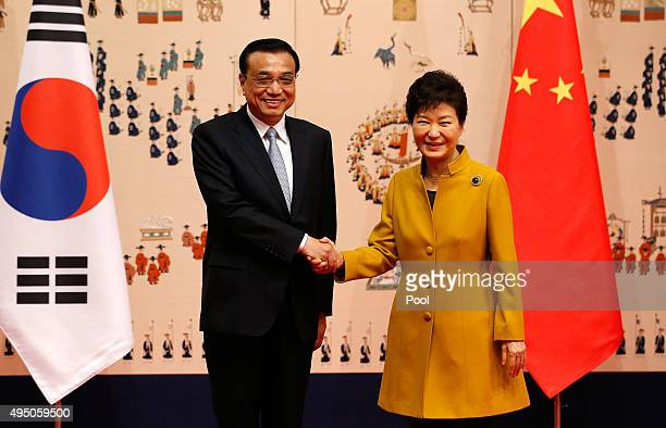 South Korean President Park Geun-Hye shakes hands with Chinese Premier Li Keqiang for their meeting at the presidential Blue House on October 31,...