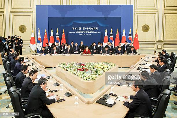 South Korean President Park GeunHye talks with Japanese Prime Minister Shinzo Abe and Chinese Premier Li Keqiang during their trilateral summit at...