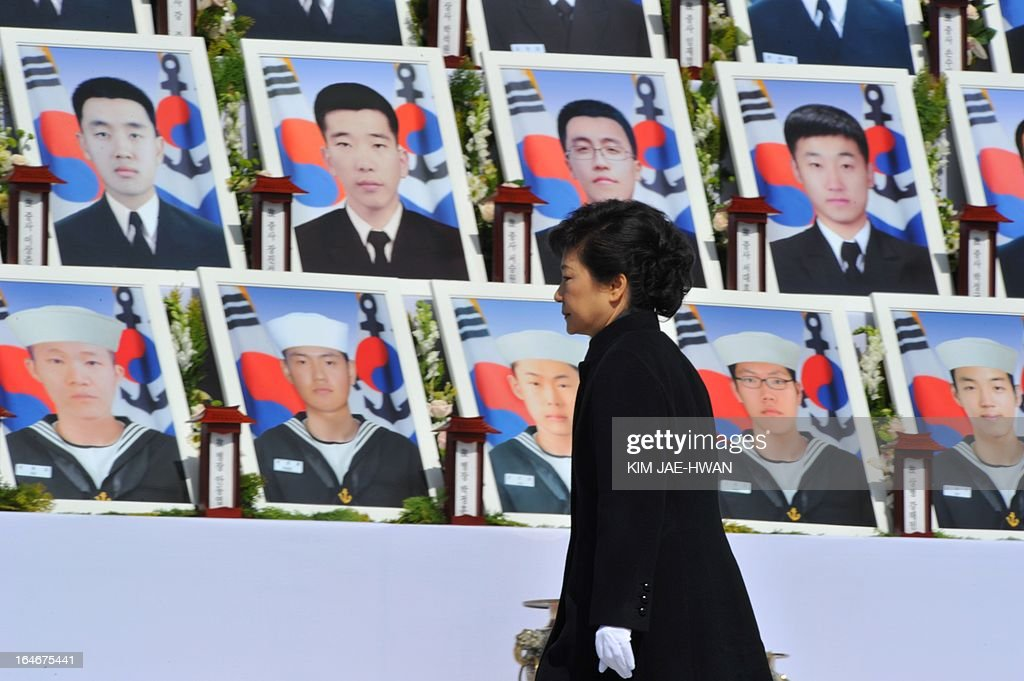 South Korean President Park Geun-Hye walks past photographs of sailors who died, during a ceremony marking the third anniversary of the sinking of a South Korean naval vessel by what Seoul insists was a North Korean submarine, at the national cemetery in the central city of Daejeon on March 26, 2013. Forty-six sailors died when the Cheonan corvette sunk.
