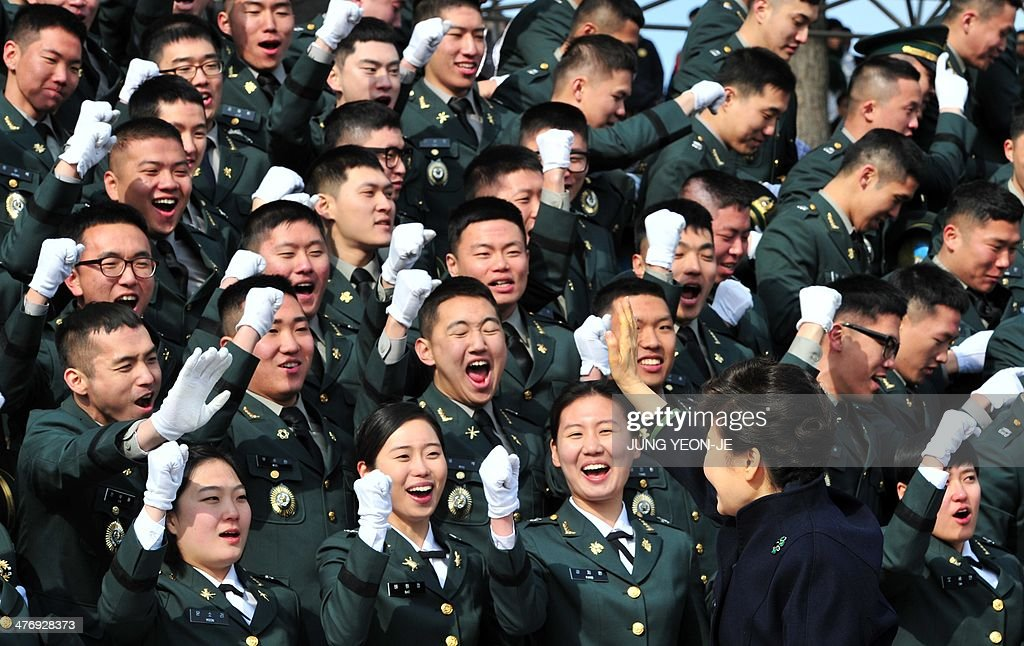 South Korean President Park Geun-Hye (R) waves to new military officers during the joint commission ceremony of 5,860 new officers of the army, navy, air force and marines at the military headquarters in Gyeryong, south of Seoul, on March 6, 2014. Park urged North Korea to give up its nuclear program, saying denuclearization will pave the way for greater economic cooperation and ultimately unification between the two divided states.
