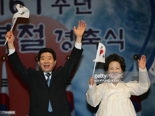 South Korean President Roh Moohyun and his wife Kwon Yangsook wave national flags at a ceremony to mark the 61th anniversary of the liberation from...