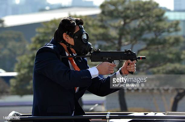 South Korean presidential body guards wearing gas masks stage an antiterror drill at the president's residence on February 27 showcasing security...