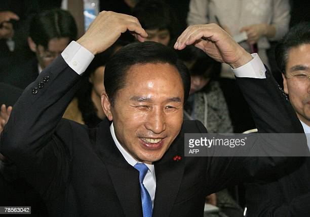South Korean presidential candidate Lee MyungBak of the opposition Grand National Party gestures with party members at their headquarters in Seoul 19...