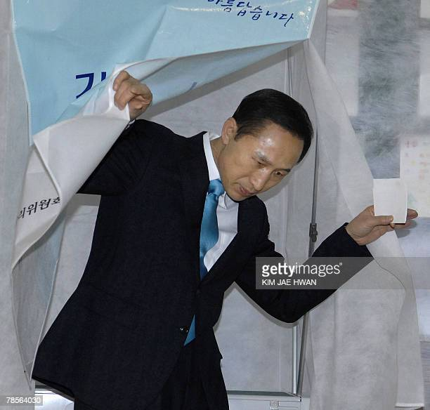South Korean presidential candidate Lee MyungBak of the opposition Grand National Party exits the voting booth before casting his ballot in the...