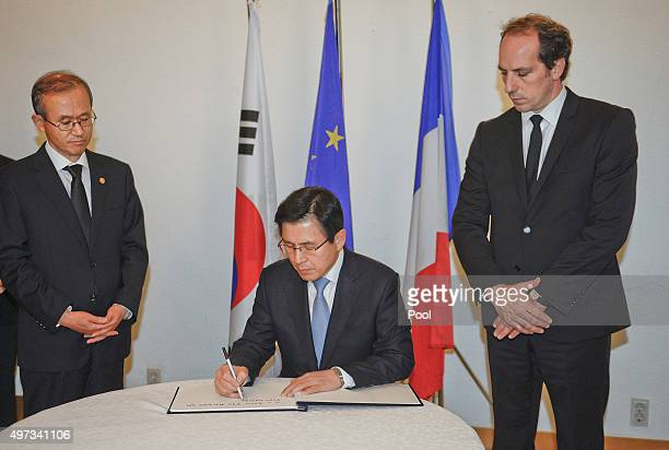 South Korean Prime Minister Hwang KyoAhn arrives to sign a book of condolences as French ambassador to South Korea Fabien Penone looks at the French...