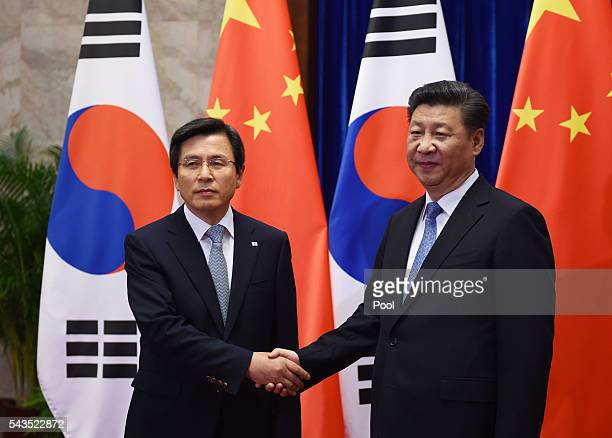 South Korean Prime Minister Hwang Kyo-ahn is greeted by Chinese President Xi Jinping before a meeting in the Great Hall of the People on June 29,...