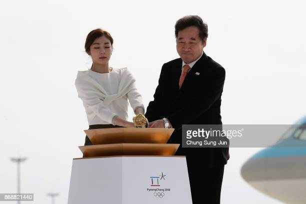 South Korean prime minister Lee Nakyon and 2010 Vancouver Olympic figure skating champion Kim YuNa light the cauldron with the Olympic flame during a...