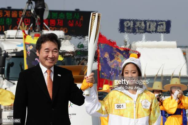 South Korean prime minister Lee Nakyon and First torch bearer South Korean figure skater You Young hold the PyeongChang 2018 Winter Olympics torch...