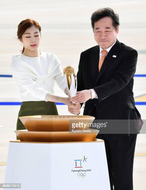 South Korean Prime Minster Lee Nak Yon and 2010 Vancouver Olympic figure skating champion Kim Yu Na light the cauldron with the Olympic flame at the...