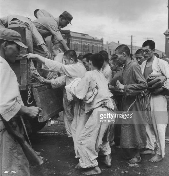 South Korean prisoners held by the South Korean army board a truck during the Korean War at Pusan where United Nations forces are based in South...