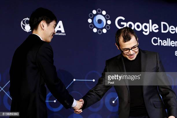 South Korean professional Go player Lee SeDol shakes hands with Demis Hassabis cofounder of Google's artificial intelligence startup DeepMind looks...