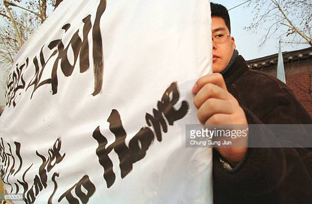 South Korean protester holds an antiAmerican sign January 12 2002 at a demonstration near the US army base in Seoul Hundreds of protesters demanded...
