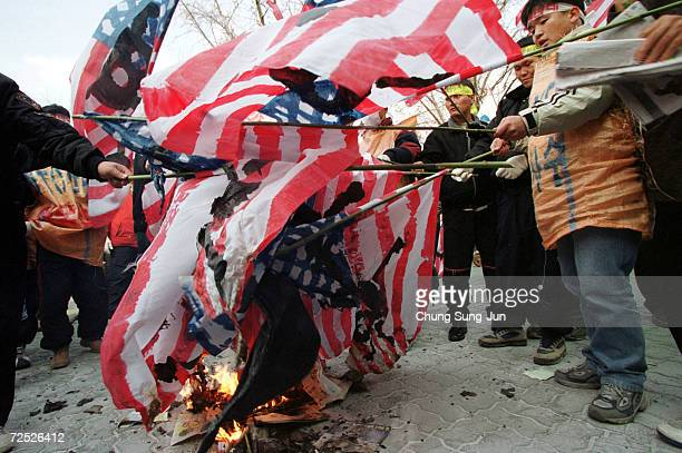 South Korean protesters burn American flags during a rally against US President George W Bushs visit to South Korea February 20 2002 in downtown...
