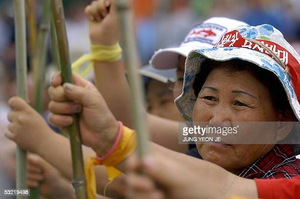 South Korean protesters hold bamboo sticks clash as they face riot policemen near a US military base in Pyeongtaek 10 July 2005 during an antiUS...