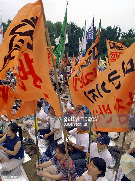 South Korean protesters hold flags reading 'opposing the relocation of US military' near a US military base in Pyeongtaek 10 July 2005 during an...