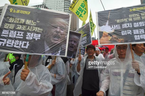 South Korean protesters hold placards showing a portrait of US President Donald Trump as they march towards the US embassy during an antiUS rally...