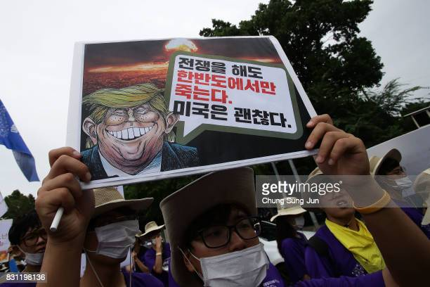 South Korean protesters hold placards with an illustration of US President Donald Trump during a rally against the deployment of the Terminal...